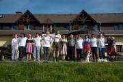 Die Mitarbeiter des Gasthofs stehen aufgereiht in einer Reihe vor dem Landgasthof und lachen in die Kamera.