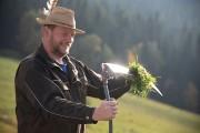 Ein Mann wischt mit einem Büschel Gras seine Sense sauber.