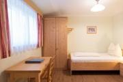 An der hinteren Wand eines Einbettzimmers befindet sich ein Bett, links befindet sich unter einem Fenster ein Schreibtisch mit Sessel.